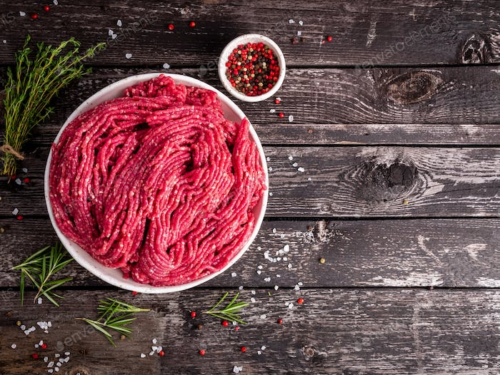 Mince beef, ground meat with ingredients for cooking on dark blue