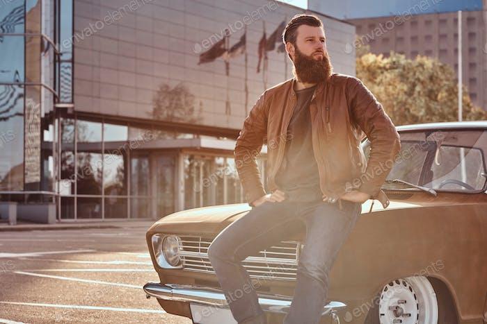 Stilvolle männliche lehnt sich auf abgestimmte Retro-Auto in der Stadt Parkplatz in der Nähe von Wolkenkratzer bei hellem Sonnenuntergang.