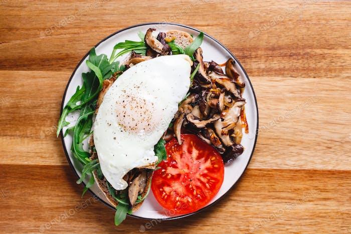 Draufsicht von zwei Sandwiches mit frischem Rucola, gebratener Shiitakepilz, Schalottenzwiebel, Ei