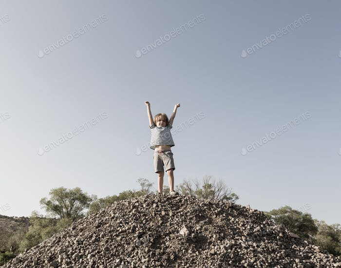 4 year old boy raising arms in triumph on top of hill