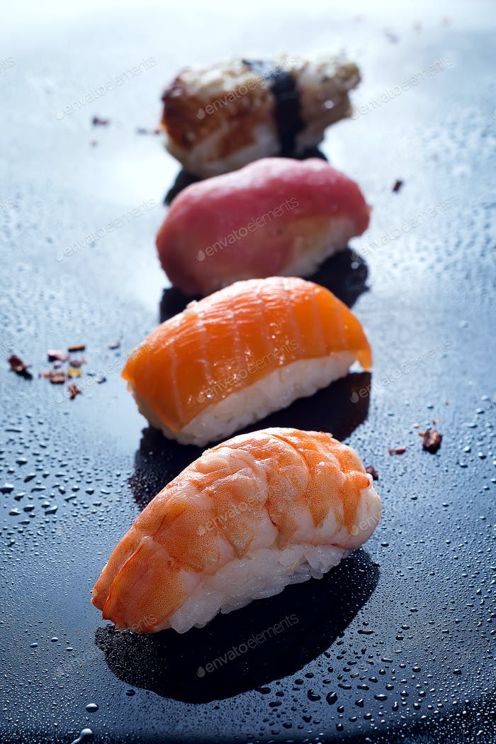 Sashimi, uramaki and nighiri, Japanese dish consisting of rice, salmon or tuna, shrimp in black with