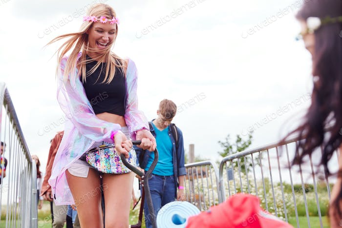 Friends Pulling Trolley As They Arrive At Music Festival Carrying Camping Equipment Onto Site
