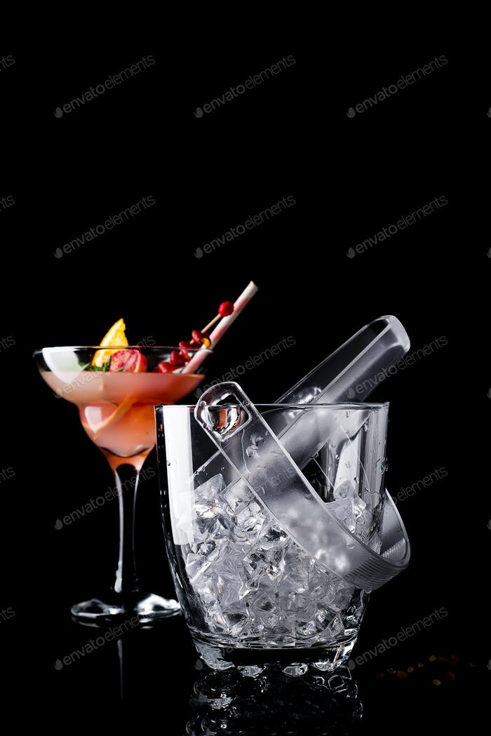 Glass ice bucket and margarita cocktail in glass isolated on black