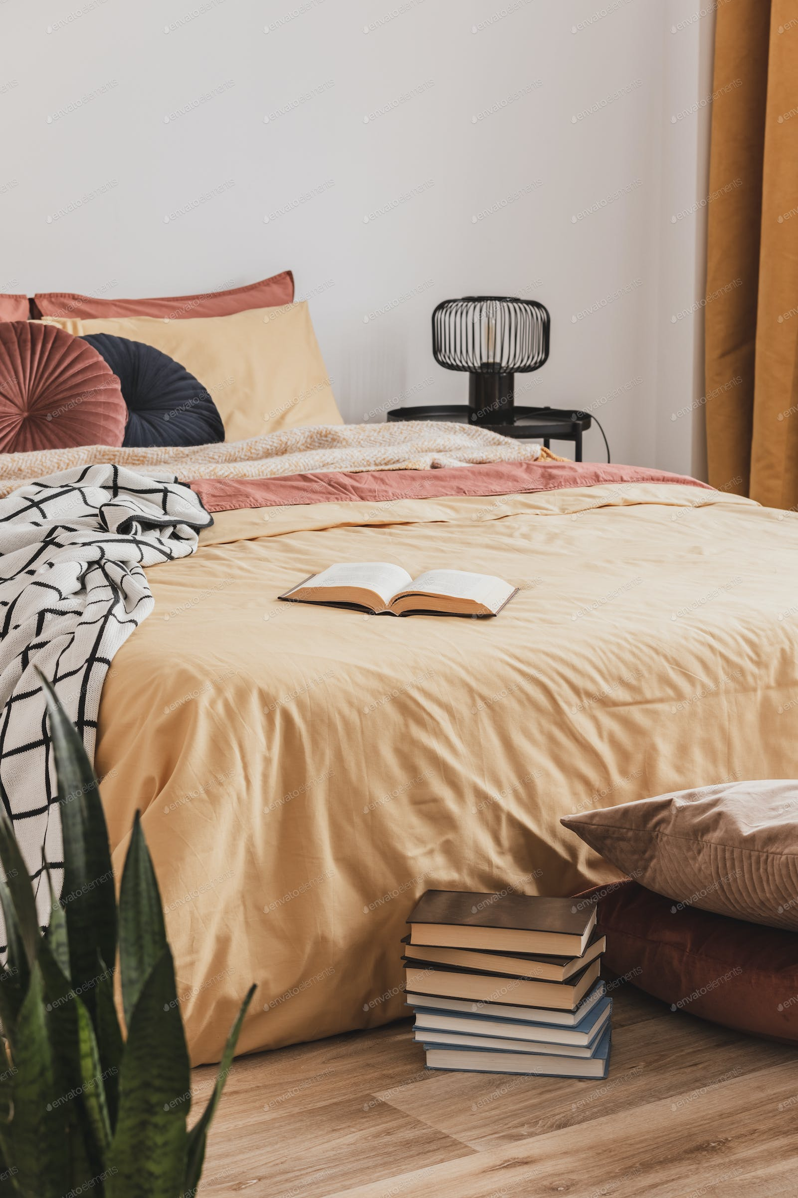 Foot Of The Bed pile of books in foot of king size bed with yellow duvet and ginger pillows  photo by bialasiewicz on envato elements