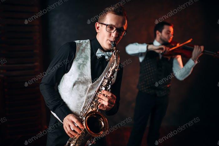 Saxofonista y violinista tocando la melodía Clásica