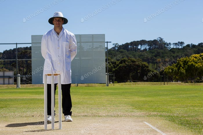 Full length of umpire standing behind stumps during cricket match