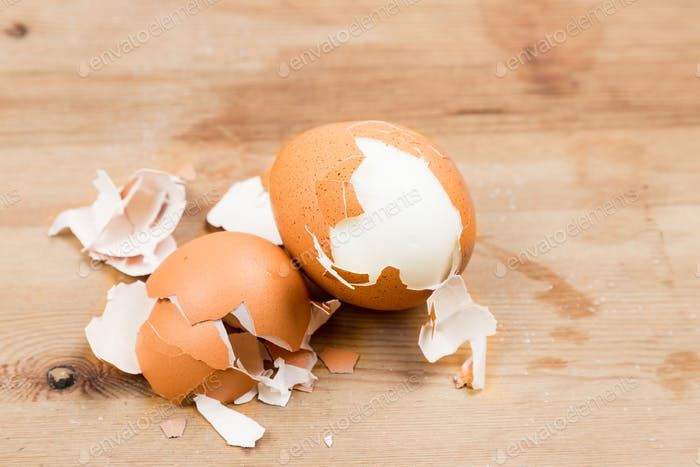 Hard boiled eggs with shell peeled on wooden table