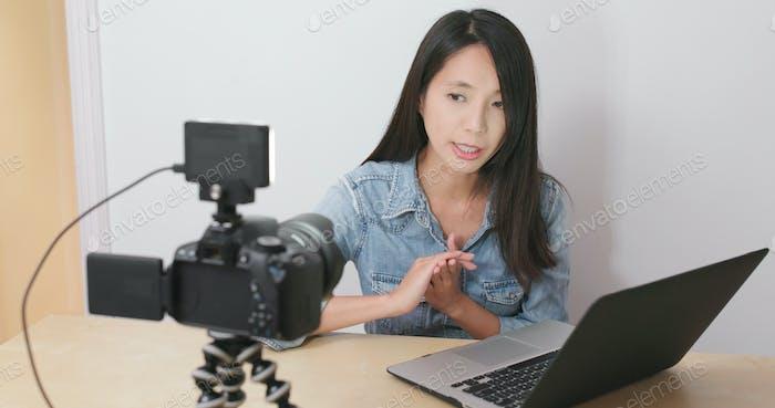 Frau nehmen Video und präsentieren mit Notebook-Computer zu Hause