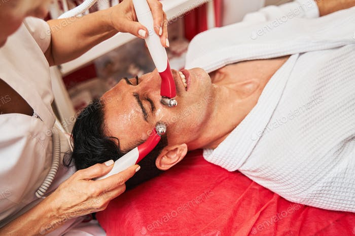 Cosmetologist rolling electric stimulation massagers on man face