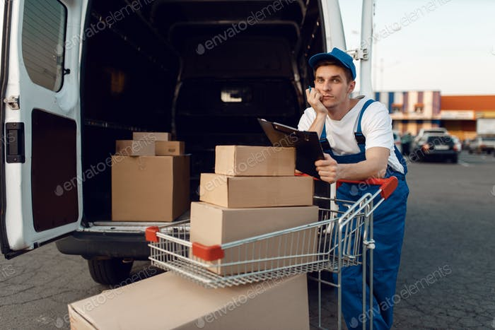 Deliveryman in uniform holds cart with boxes