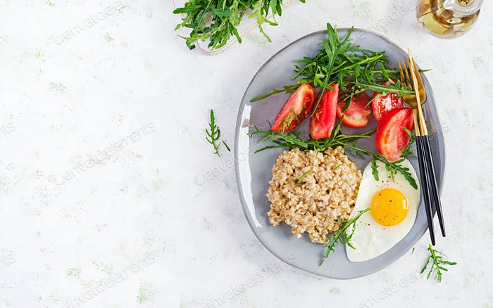 Breakfast oatmeal porridge with fried egg, tomatoes, arugula