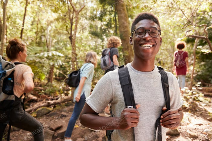 Waist up portrait of smiling millennial African American man hiking in a forest with friends