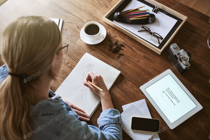 Female entrepreneur sketching on a notepad in her home office