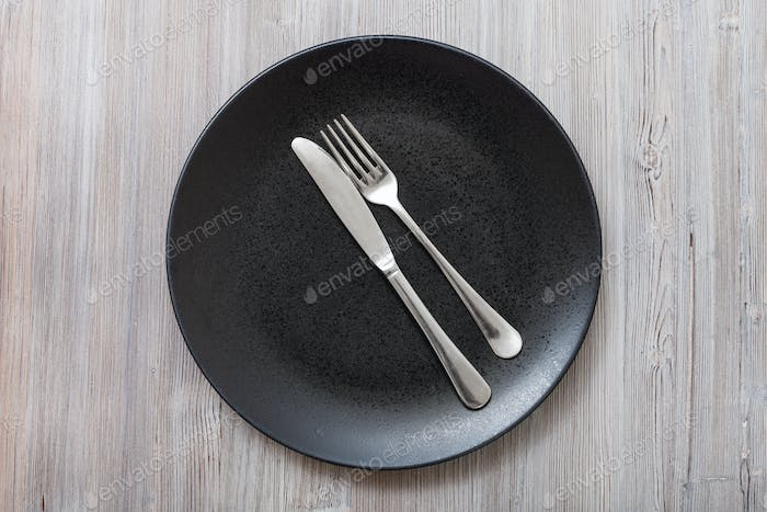 top view of black plate with cutlery on gray