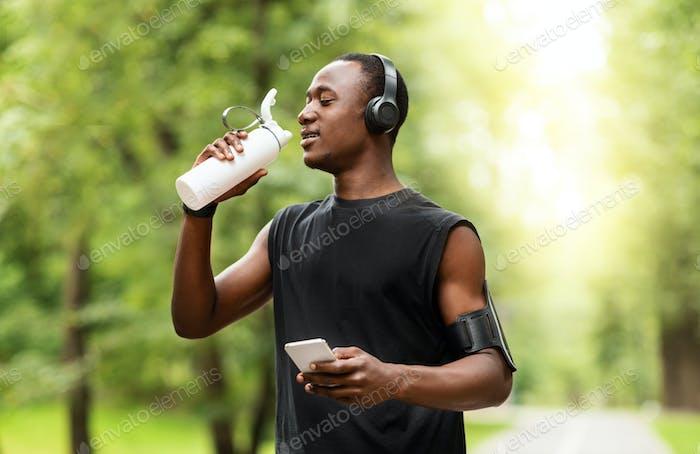 Afrikanischer Jogger Trinkwasser und mit Smartphone
