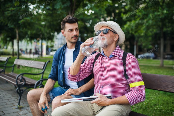 Young man and blind senior with white cane sitting on bench in park in city