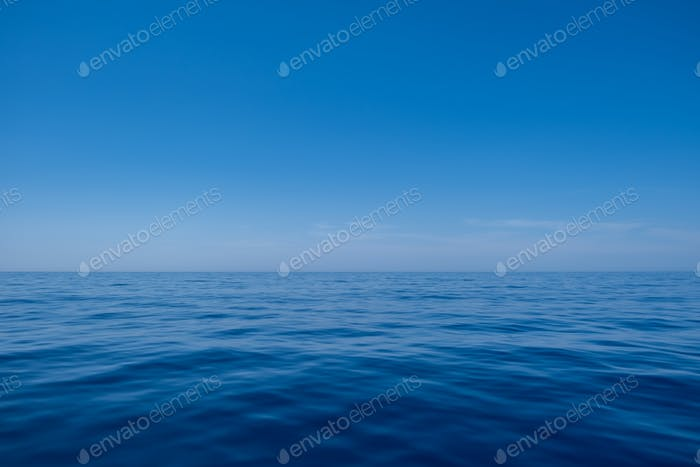 Sea water surface calm with small ripples, deep blue color and blue sky background,