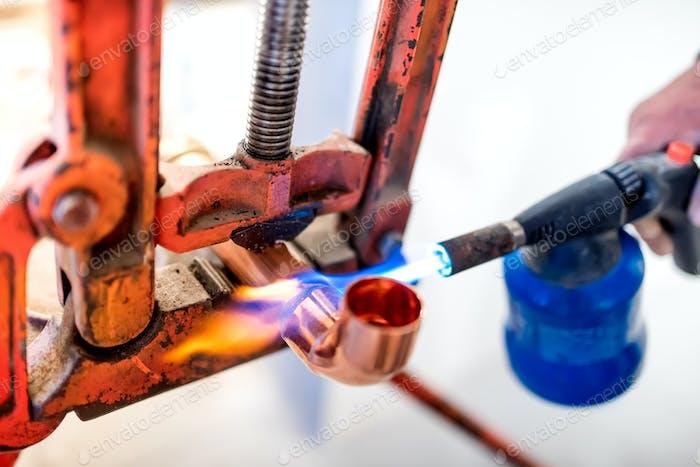 Industriearbeiter mit Propangasbrenner zum Löten von Kupferrohren.