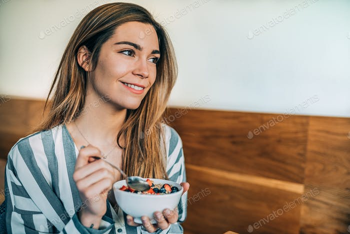 woman close up eating oat and fruits bowl for breakfast