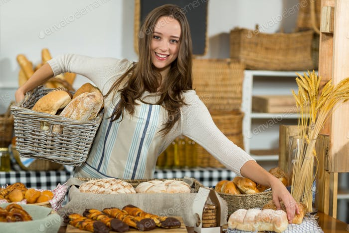 Portrait of smiling female staff holding breads in wicker basket at counter
