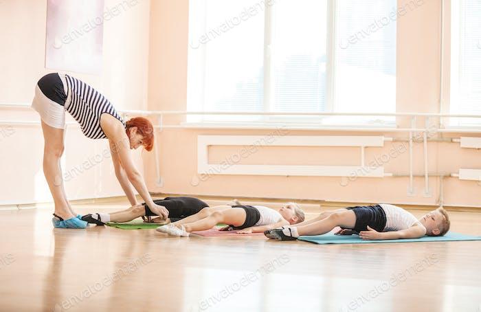 Преподаватель балета помогает молодым студентам выполнять упражнения на полу