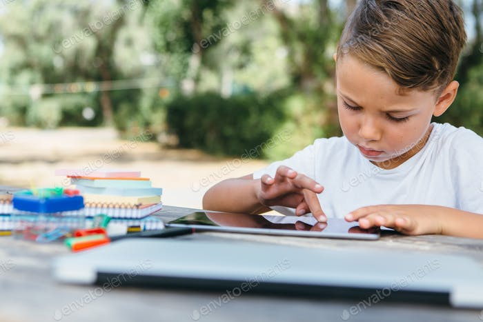 Kid browsing tablet doing homework