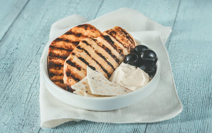 Grilled chicken breast with black olives and tahini sauce