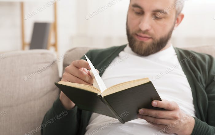 Close up of bearded man reading book at home