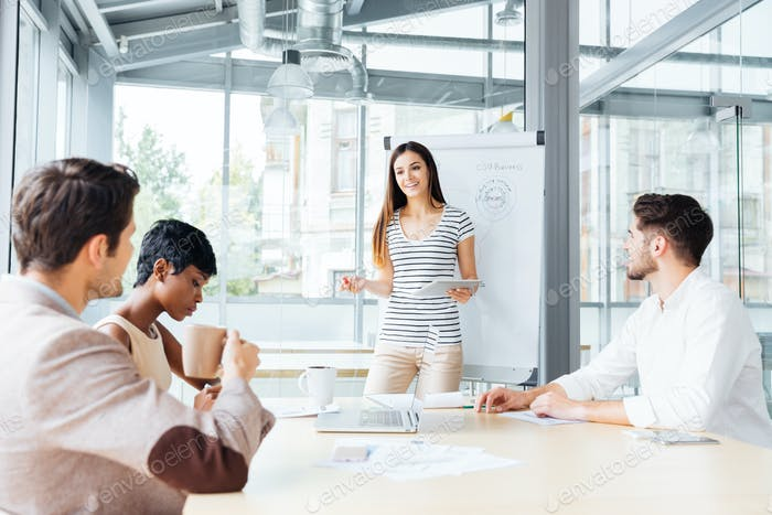 Smiling woman making presentation for business people in office