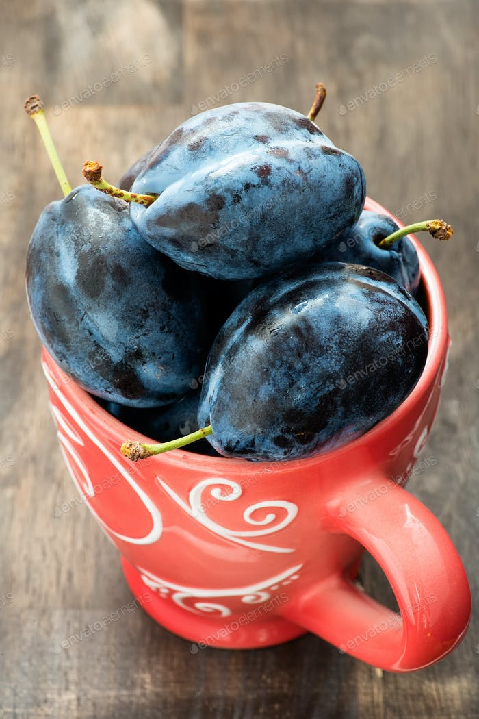 Fresh plums in cup over wooden background