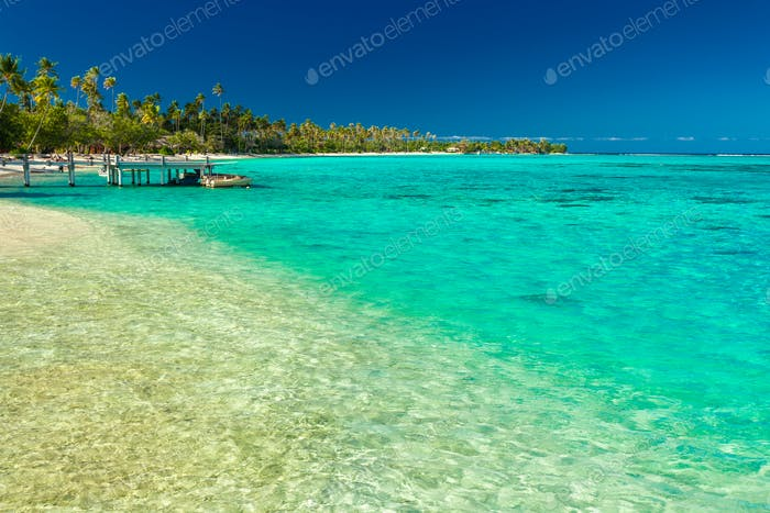 Little jetty and boat on tropical beach with amazing water, Moor