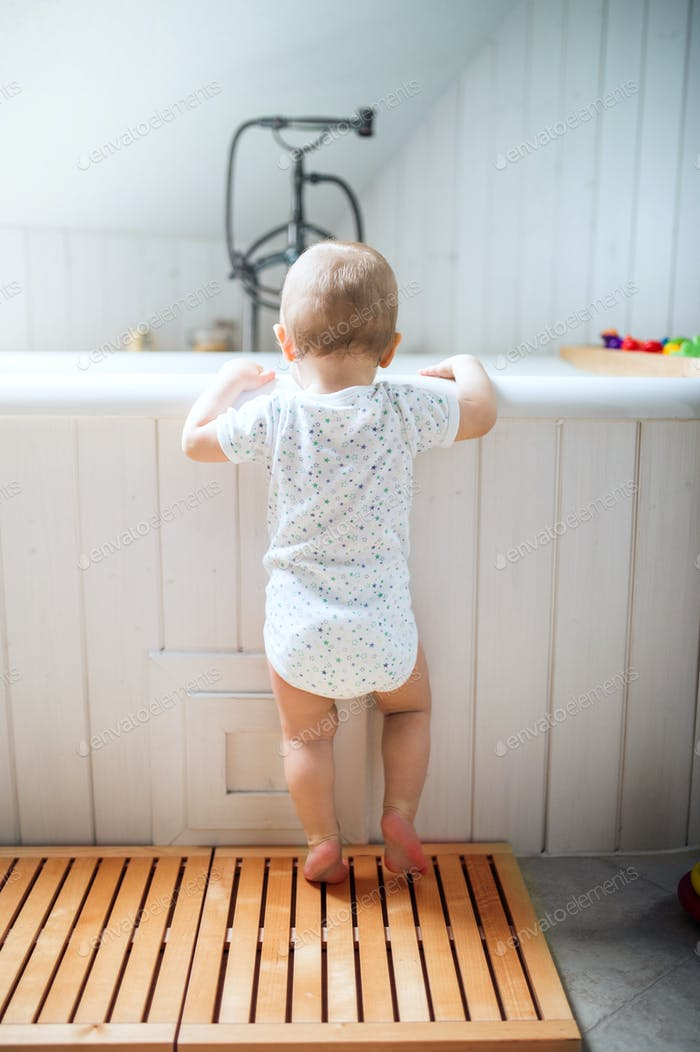 A toddler child standing at the bath in the bathroom at home.