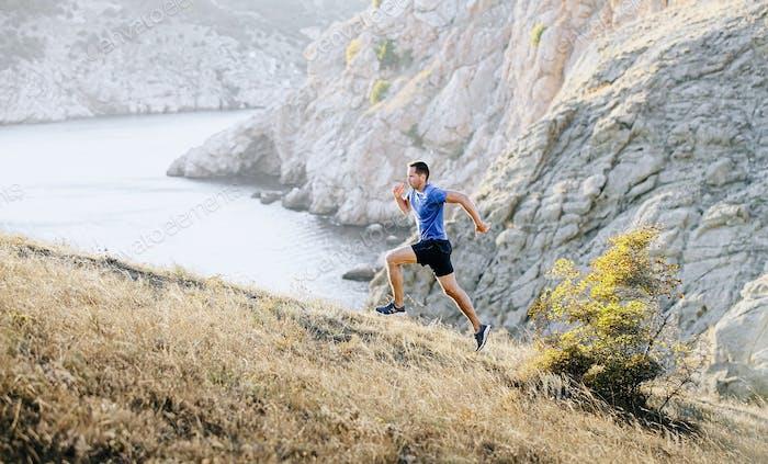 Mann Athlet dynamisches Laufen bergauf