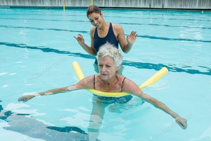 Female coach helping senior woman in swimming pool