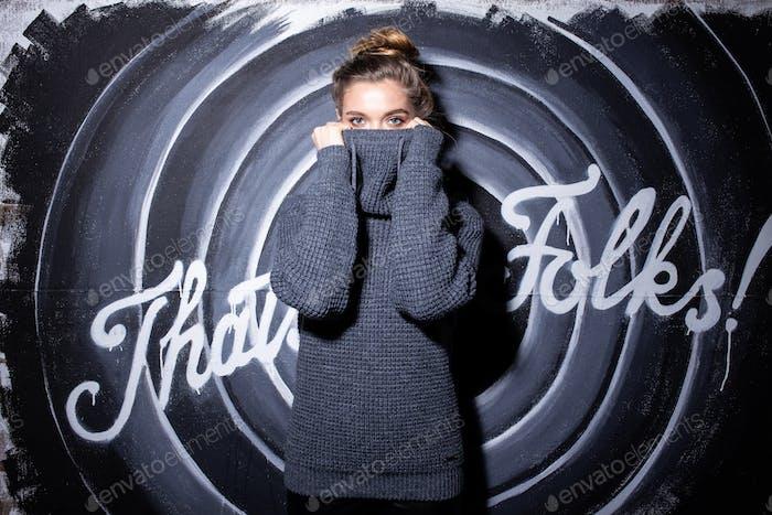 Porträt eines jungen modischen Mädchens in einem grauen Pullover stehend in der Nacht auf der Straße gegenüber der