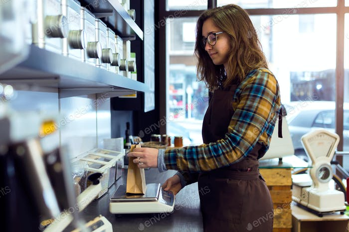 Beautiful young saleswoman weighing coffee beans in a retail sto