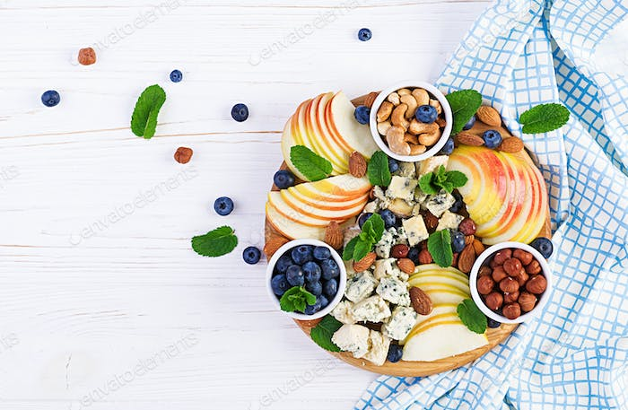 Cheese platter with assorted cheeses, blueberry, apples, nuts on white table.
