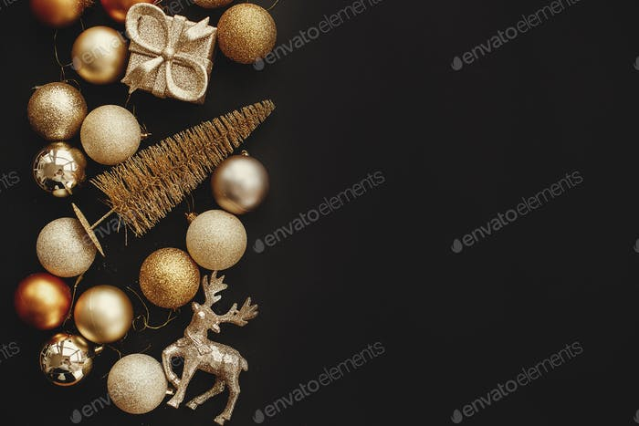 Christmas golden gift box, tree, reindeer and glitter baubles on stylish black background