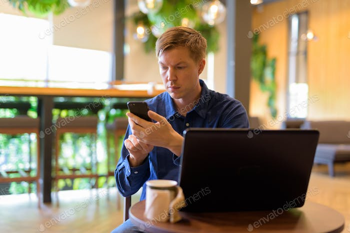 Young handsome businessman using phone while working at the coffee shop