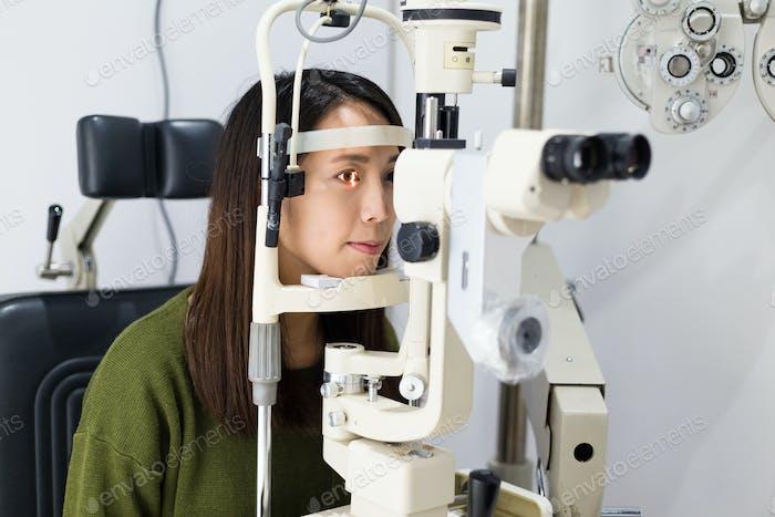 Woman doing eye test in optical clinic