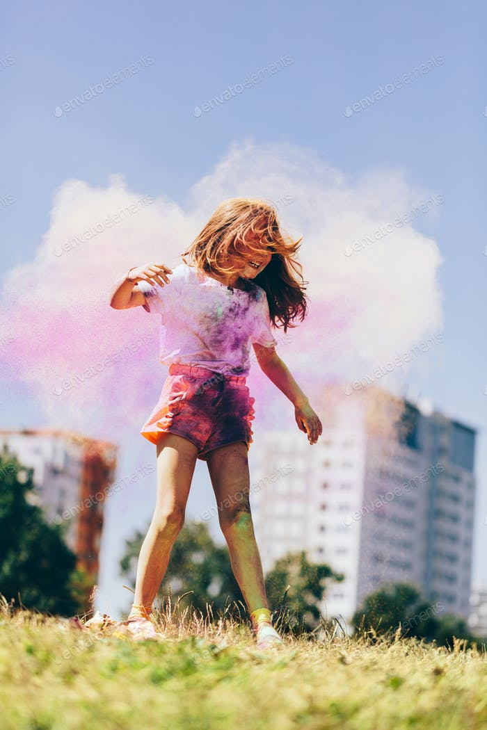 Little girl playing in colorful clouds of holi powder