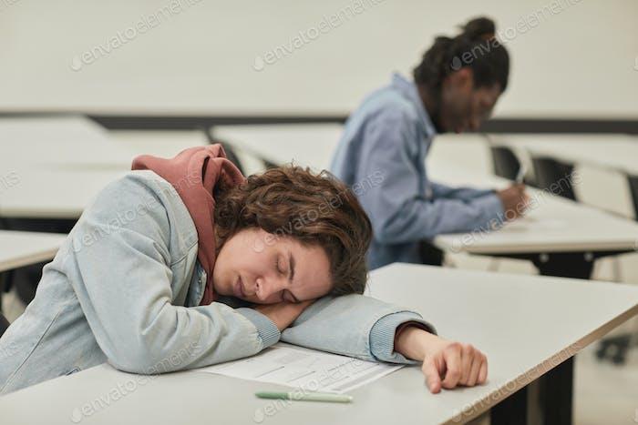 Teenage boy sleeping in class