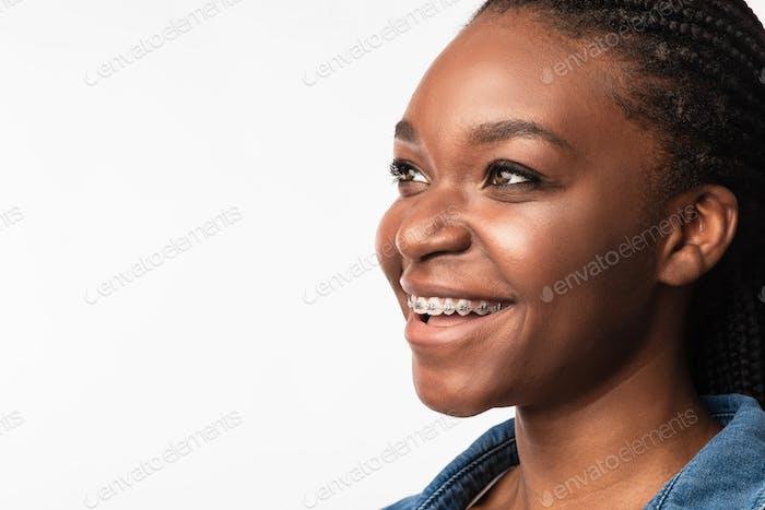 Mädchen mit Zahnspange, das auf weißem Hintergrund zur Seite schaut