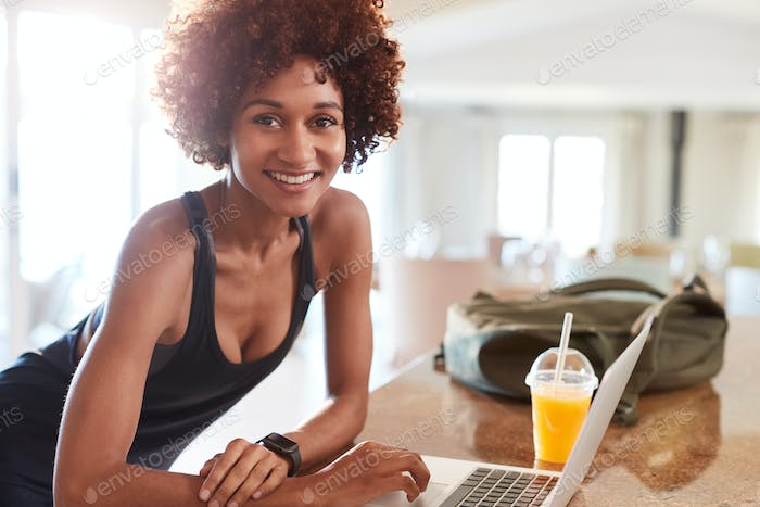 Millennial African American woman checking fitness data on laptop after gym smiling to camera