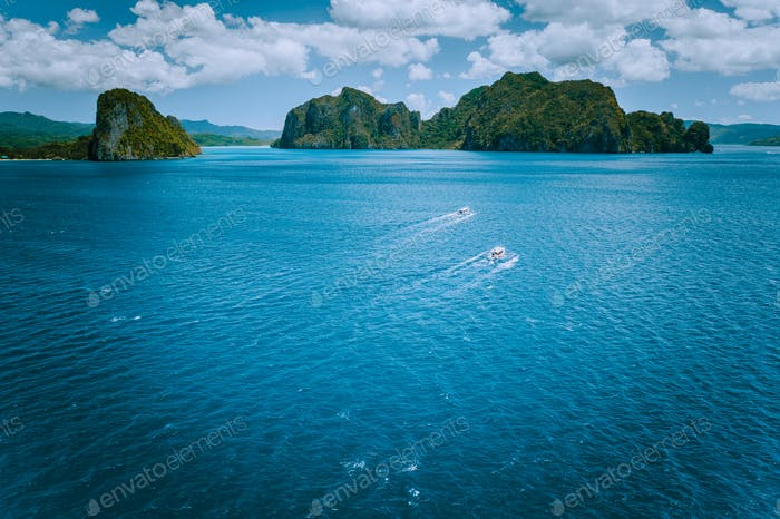 Aerial view of island hopping boats on open waved sea on the way to tour B in picturesque