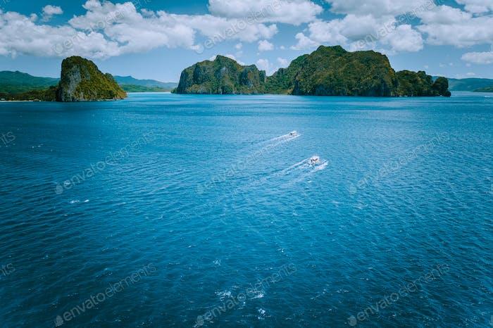 Luftaufnahme von Inselhüpfbooten auf offenem Wellenmeer auf dem Weg zur Tour B in malerischer