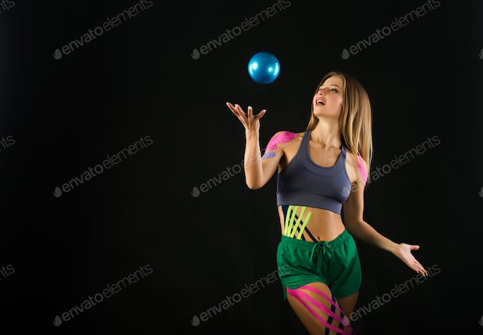 Girl trains with ball, color tapes