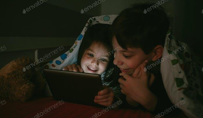Brüder schauen im Dunkeln auf das Tablet