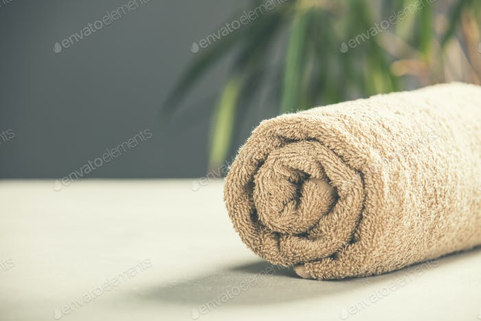 Brown Towel on concrete background - SPA and relaxation concept