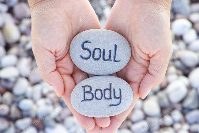 Woman holding stone with the words Soul and Body in her palms